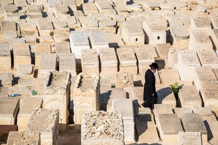 middle east fighting: Jerusalem, Israel - November 1, 2015: Orthodox Jew walking among graves on the Mount of Olives cemetery.