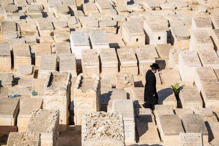 Jerusalem, Israel - November 1, 2015: Orthodox Jew walking among graves on the Mount of Olives cemetery.