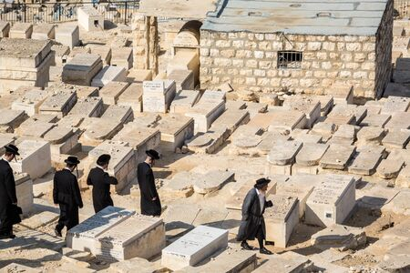 jews: Jerusalem, Israel - November 1, 2015: Orthodox Jews walking among graves on the Mount of Olives cemetery.