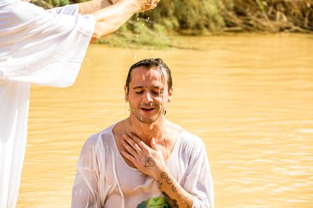 Jericho, Israël - 2 november 2015: Georganiseerde doop voor groep pelgrims in de rivier de Jordaan, de plaats die wordt verondersteld dat Jezus werd gedoopt