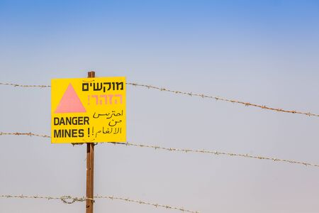 mines: Danger Mines! Warning sign and barbed wire. Israeli border with Jordan