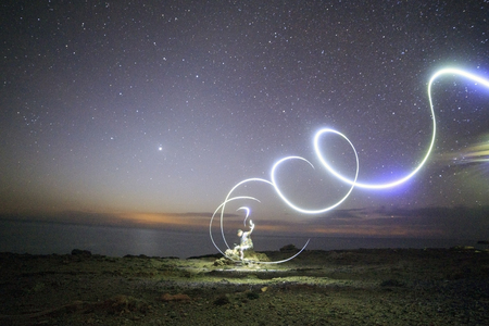 Lonely man sitting on rock surrounded by swirling light