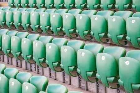 Green plastic seats on the tribune at modern stadium