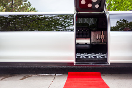 White limousine with inviting open door and red carpet