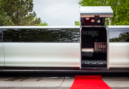 invitando: White limousine with inviting open door and red carpet