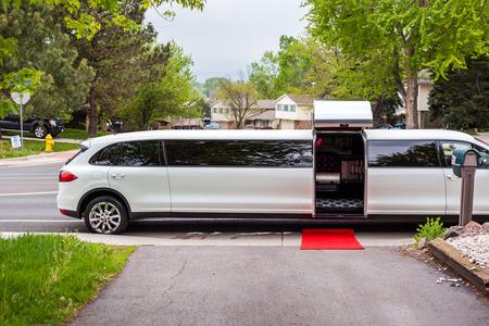 Witte limousine met uitnodigende open deur en rode loper