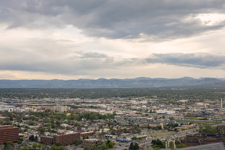 denver skyline with mountains: Denver residential buildings at suburbs and Rocky mountains in Colorado, USA