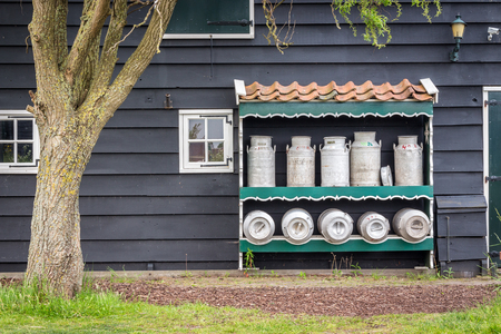 milk containers: Vintage milk containers with grey, wooden house behind. Stock Photo