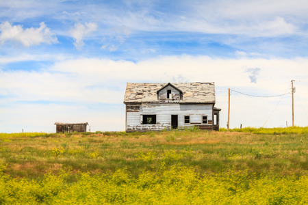 Abandoned white house in the middle of the meadow Stock Photo