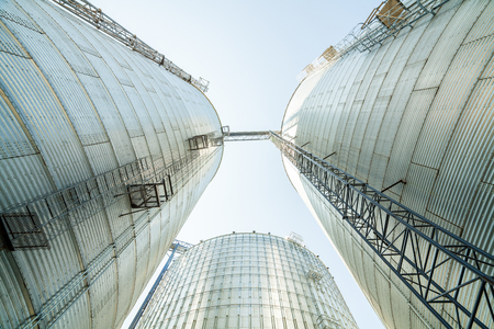 Huge, silver, shining agricultural silos on a farm, USA