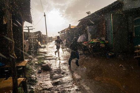 Boys running through african market during rain, Kenya Imagens - 70817595