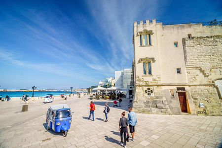 Otranto, Italy - April 24, 2017: Tourists enjoying seaside promenade by historic architecture.