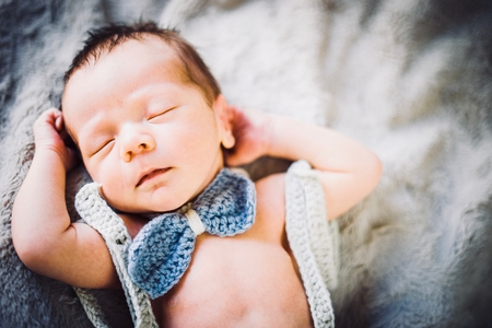 A newborn baby boy sleeping in blue and grey knitted bow tie and trousers