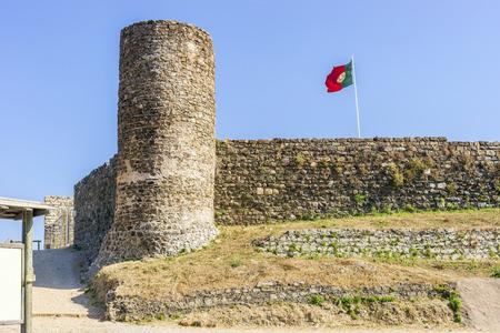 Castle in Aljezur with waving portuguese flag, Algarve, Portugal Foto de archivo