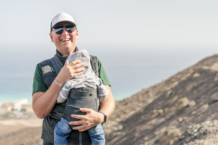 Father with his 9 months son in baby carrier on the trail in the mountains Stok Fotoğraf