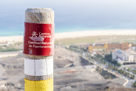Post on the Fuerteventura mountains informing hikers about the trail. Sign says: Natural trail. Natural trails of Fuerteventura.