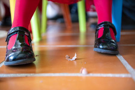 Little girl wearing pumps shoes with pencil shavings on the floor