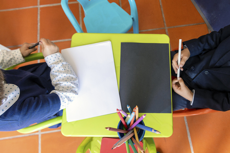 Two kids sitting by small table with crayons and paper sheet ready to  draw Stok Fotoğraf
