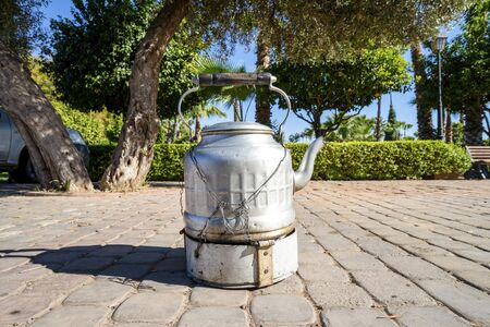 Strong black coffee in silver kettle sold by street vendor in Marrakech, Morocco Standard-Bild