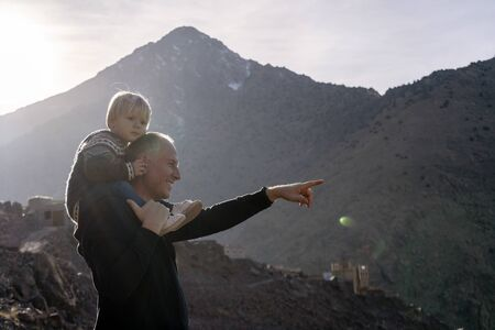 Father showing beauty of nature to his small boy in Atlas mountains, Morocco Foto de archivo