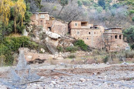 Small berber village by river in Atlas mountains, Morocco