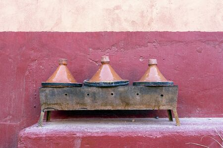 Three clay tagine pots on portable barbeque