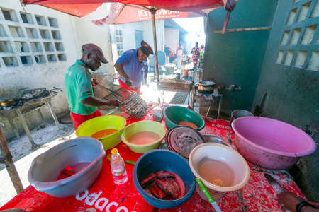Maputo, Mozambique - May 12, 2019: two restaurant's workers grilling fish previously marinated in a sauce 報道画像