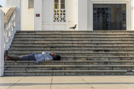 A man resting on the stairs in front of cathedral of Maputo, Mozambique