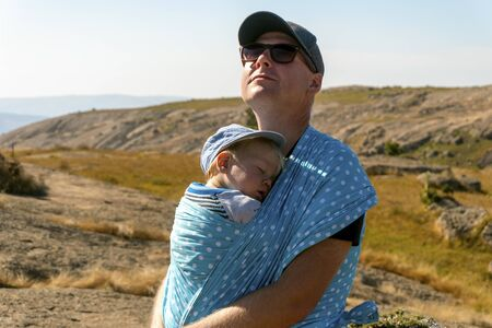 Father with his sleeping baby boy in sling enjoying nature, Swaziland