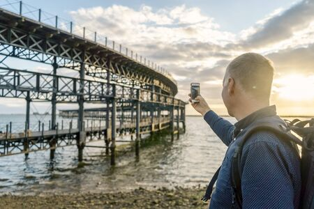 Tourist taking photo of historic Rio Tinto Pier by sunset in Huelva, Andalusia, Spain