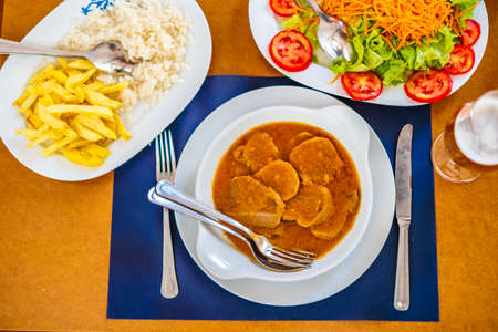 Traditional food from Alentejo - cow's tongue in a sauce served with salad, rice and french fries, Portugal, Europe