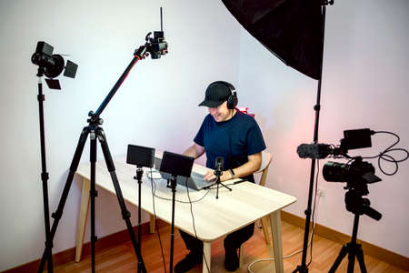 Gamer, streamer, or Youtuber streaming and recording in his home studio Imagens