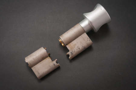 Lock cylinder with knob broken in the middle. Cylinder was pulled during an attempted break-in and was destroyed as a result. The background is black