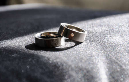 Wedding rings on a dark surface. Uniquely decorated with lasered fingerprints and a diamond