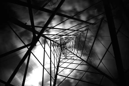 discharge time: Electricity Pylon with clouds moving in Black and White Stock Photo