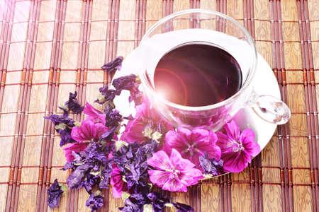 fiori secchi: L'infusione di fiori freschi e secchi malva sulla tovaglia di bamb�. Texture sovrapposizione floreale. Riflessione sulla tazza.
