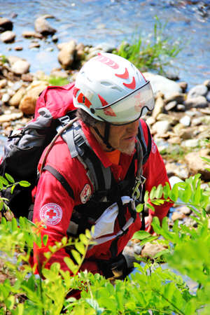 Demonstration of the activity of the Italian civil protection components held in the provinces of Turin Italy in June 2015. The rescuer with his dog perform a search for a missing person along the bank of the river. The Canine Unit of the Italian Red Cros Editorial