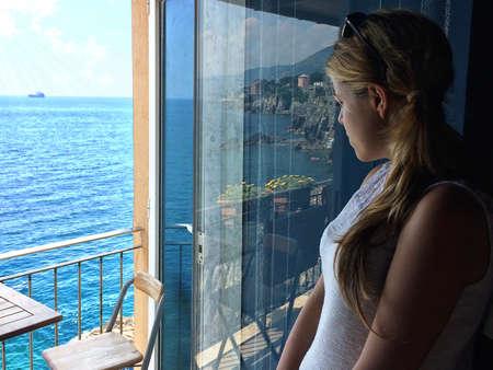 mujer mirando el horizonte: Chica Reloj mar desde el balcón. Chica joven que mira a la costa de Liguria desde el balcón de una heladería, Nervi Génova GE Italia. Foto de archivo