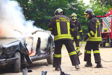 firefighter: Firefighters extinguishing car on fire. Demonstration switching off a car in flames by the Italian firefighters volunteers. Demonstration held in the province of Turin in Piedmont Italy Stock Photo
