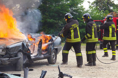 accident fire truck: Firefighters extinguishing car on fire. Demonstration switching off a car in flames by the Italian firefighters volunteers. Demonstration held in the province of Turin in Piedmont Italy Stock Photo