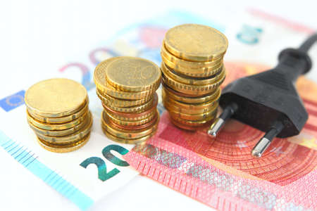 cardioverter: Electric plug with money and coins. Energy saving concept. Soft and selective focus. Stock Photo