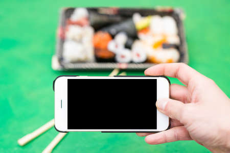 darck: Bowl of sushi photographed by smartphone. Smartphone with darck screen, possible text space  Stock Photo