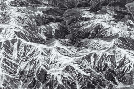 Complex of mountains seen from the air. Black and white version.
