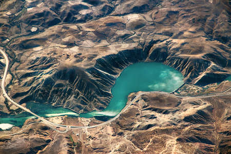 Complex of mountains and dam seen from the air.