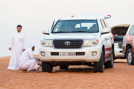 DUBAI, UNITED ARAB EMIRATES - 31 Ott, 2016: Crowd in the desert. Desert that surrounds the city of Dubai. Group of tourists make a safari with 4x4 car in the desert dunes.