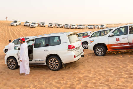DUBAI, UNITED ARAB EMIRATES - 31 Ott, 2016: Crowd in the desert.Desert that surrounds the city of Dubai. Group of tourists make a safari with 4x4 car in the desert dunes. Sajtókép