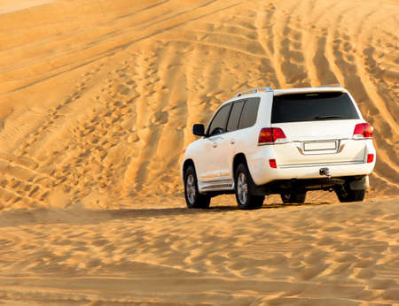 SUV in the desert. dunes and footprints in the sand. Text space. No people. Stock fotó