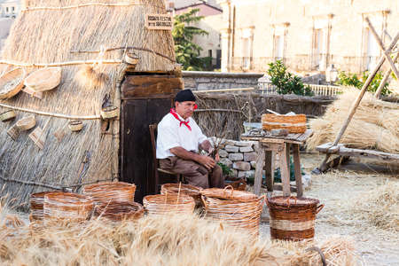 August 18, 2017 - Gangi, Sicily Italy. Man builds a wicker basket with traditional Sicilian clothes. Representation of a camp used during wheat harvest.