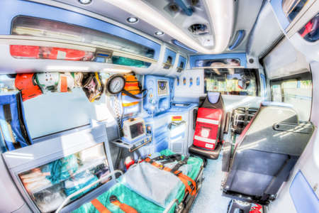 Inside the ambulance, view from the sanitary compartment. Different medical equipment and a stretcher. Selective focus, high key.