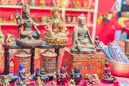 Ethnic objects on a stand. Ornamental gold statuettes representing ethnic, Indian, Hindu and Buddhist deities